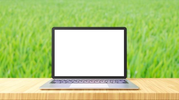 녹색 쌀 농장 배경으로 나무 테이블에 노트북 컴퓨터 은색 장소. 3d 그림 렌더링 이미지입니다.