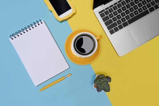 Портативный компьютер, смартфон и кофейная чашка на двухцветном синем и желтом фоне.