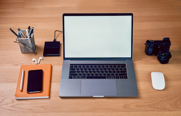 Laptop computer and smartphone in creative office, blank screen on mockup for design advertising.