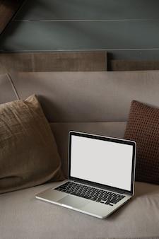 枕付きソファに空白のコピースペース画面ディスプレイを備えたラップトップコンピュータ