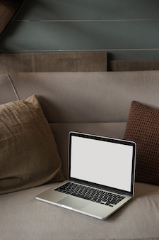 Laptop computer with blank copy space screen display on sofa with pillows
