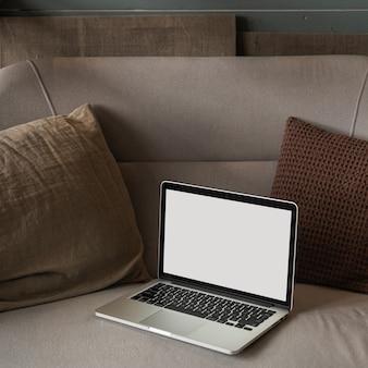 枕が付いている快適なソファーの空白のスクリーンが付いているラップトップコンピュータ