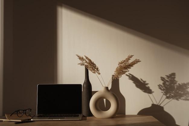 壁の日光の影にパンパスグラスの花束とテーブルの上の空白の画面とラップトップコンピューター