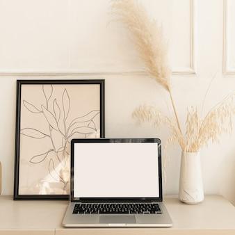 Boho 장식 테이블에 빈 화면 파스텔 베이지 색 노트북 컴퓨터. 팜파스 잔디 꽃다발, 가정 식물.