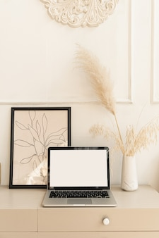 Laptop computer with blank screen pastel beige on table with boho decorations. pampas grass bouquet, home plant.