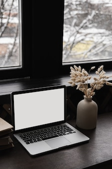 Laptop computer with blank screen on table with books stack, bunny rabbit tail grass bouquet.