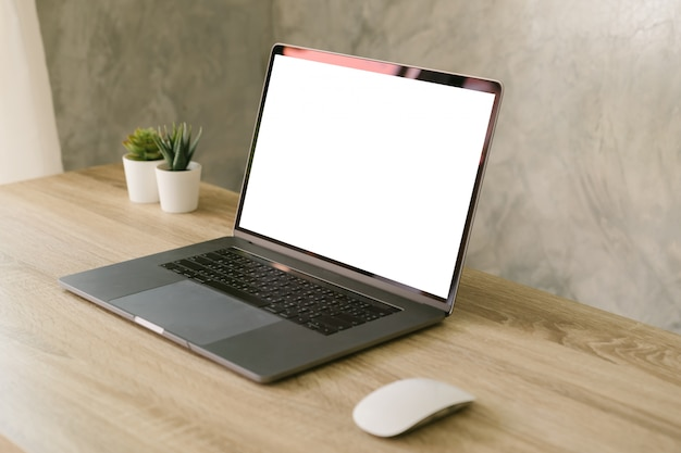 Laptop computer with blank screen on table.