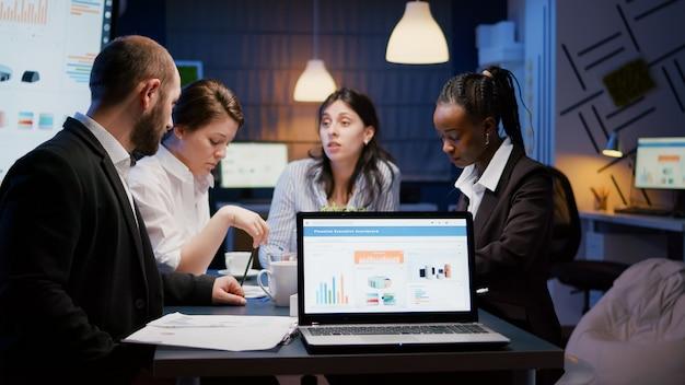 Портативный компьютер с презентацией финансовых графиков на мониторе, стоящем на конференц-столе в конференц-зале поздно ночью