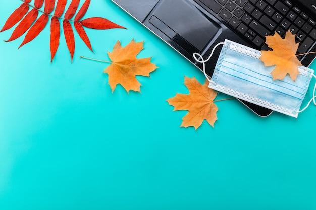 パンデミックの概念の間に秋のマスクとラップトップコンピューター