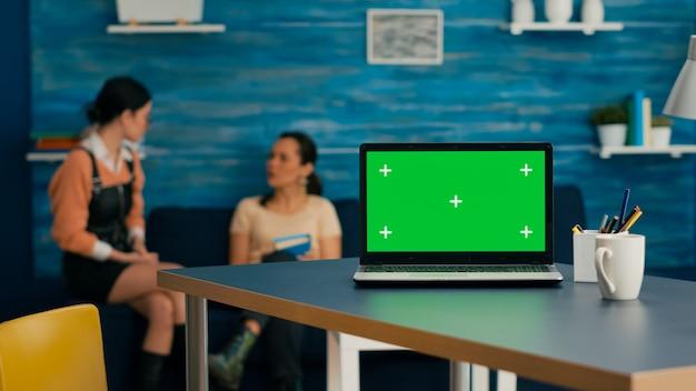 バックグラウンドでビジネスコマースについて話している2人の女性が机の上に立っているモックアップグリーンスクリーンクロマキーを備えたラップトップコンピューター。ホームスタジオには強力な分離pcが装備されています
