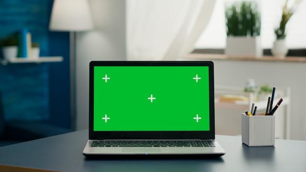 誰もいないホームオフィスの机の上に立っているモックアップグリーンスクリーンクロマキーを備えたラップトップコンピューター。プロフェッショナルなセットアップは、分離されたpcを使用したeコマースコースの準備ができています