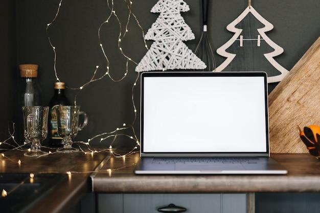 クリスマスの装飾が施されたキッチンテーブルに、白い空白の画面がモックアップされたラップトップコンピューター。