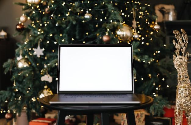 Портативный компьютер с макетом белый пустой экран, на столе возле елки.