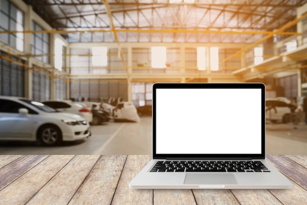 Laptop computer on wooden table with blurred car service centre background