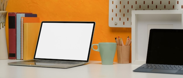 Laptop on creative office desk with digital tablet, stationery, books and decorations
