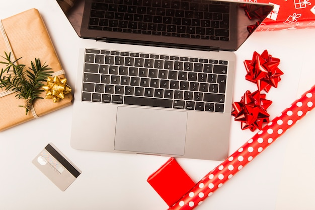 Laptop and credit card with christmas wrapped gift on table