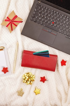 Laptop, credit cards, purse and christmas decoration. online christmas shopping, buying gifts