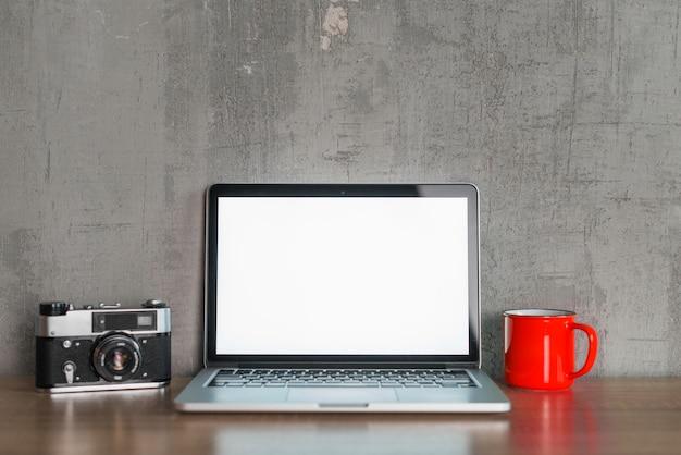 휴대용 퍼스널 컴퓨터; 컵과 나무 책상에 카메라