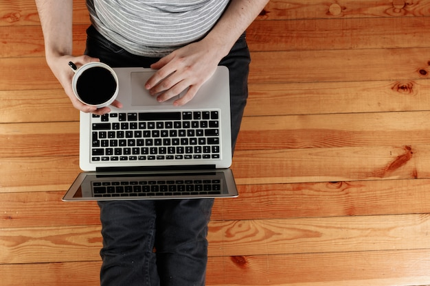 A laptop and a cup of coffee in the hands of a man sitting on a wooden floor.