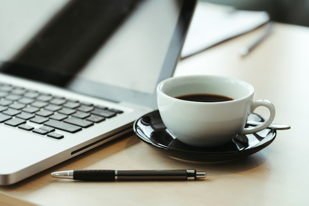 Laptop and cup of coffee on old wooden table