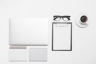 Laptop; cup of black coffee and office stationeries isolated on white backdrop