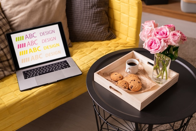 Laptop and cushions on yellow couch by small table with wooden box containing bunch of pink roses, drink and tasty cookies