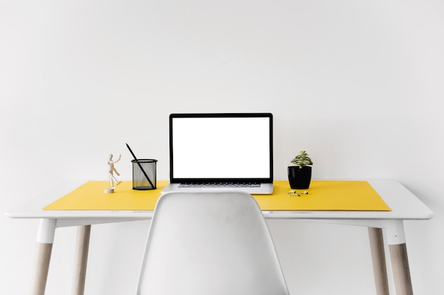Laptop on desk against white wall