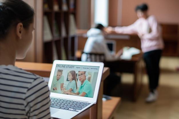 教育ウェブサイトのホームページと現代の10代の学生が前に座って勉強しているラップトップディスプレイ
