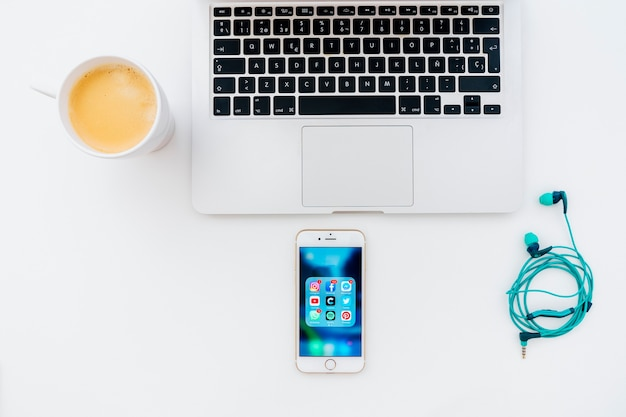 앱으로 가득 찬 노트북, 이어폰, 커피 및 전화