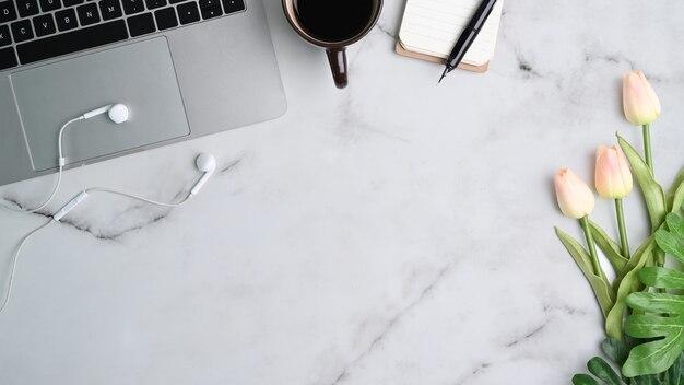 Ноутбук, наушники, кофе, блокнот, карандаш и цветок тюльпана на рабочем месте мраморного стола.