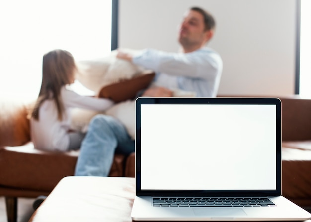 Laptop in front of daughter and father playing with pillows