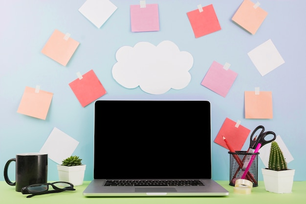 Laptop in front of wall with cloud paper and adhesive notes