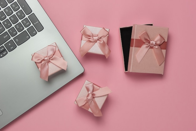 Laptop and gift boxes with bows on pink pastel background. composition for christmas, birthday or wedding. top view