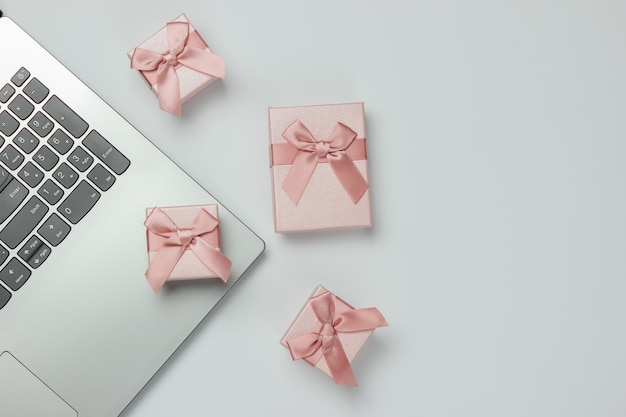 Laptop and gift boxes with bows on white background. composition for christmas, birthday or wedding. copy space. top view