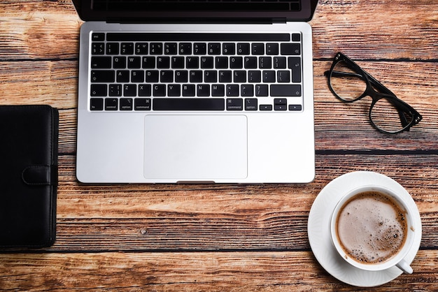 Laptop, glasses, notepad and a cup of coffee on a wooden table top view. vacation or online shopping concept