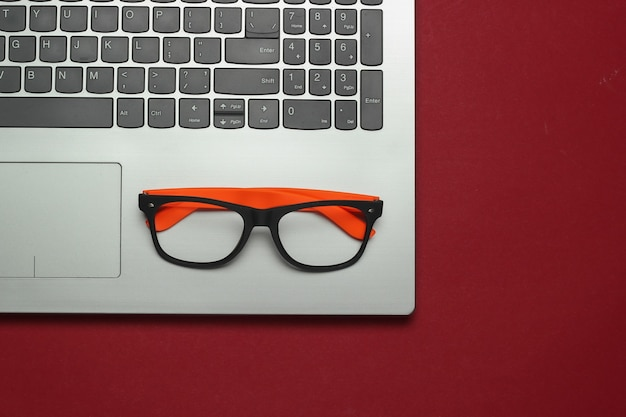 Laptop and glasses without lenses on red background. freelance concept. flat lay. top view
