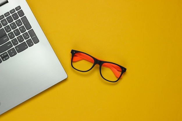 Laptop and glasses without lenses on yellow background. freelance concept. flat lay. top view