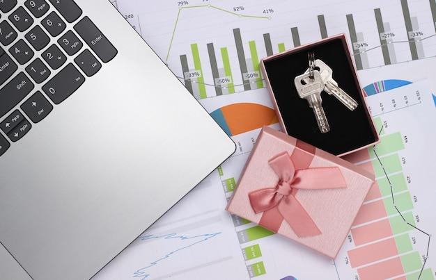 ノートパソコン、グラフとチャート、キー付きギフトボックス。事業計画、財務分析、統計。上面図
