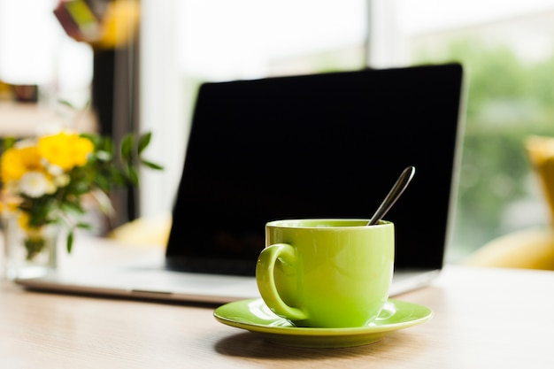 Laptop and green ceramic coffee cup on work desk