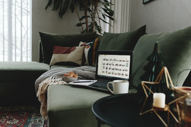 Laptop on the green sofa. work from home. loft or modern interior.