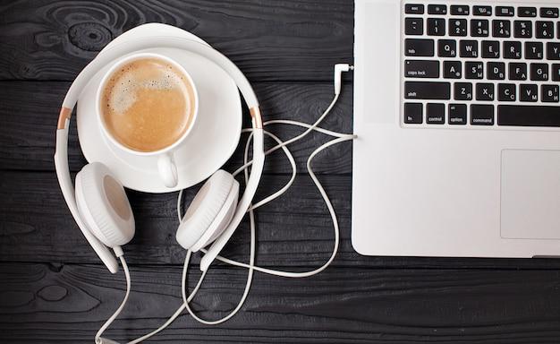 Компьтер-книжка, наушники и кофейная чашка на черном деревянном столе. вид сверху с копией пространства
