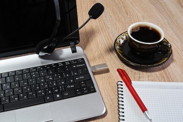 ノートパソコン、マイク付きヘッドフォン、ペン付きノートブック、テーブルの上のコーヒーカップをクローズアップ