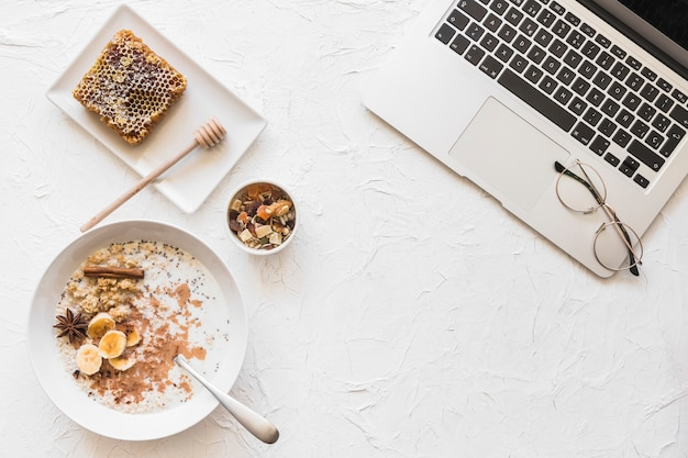 Laptop and healthy breakfast on rough white backdrop