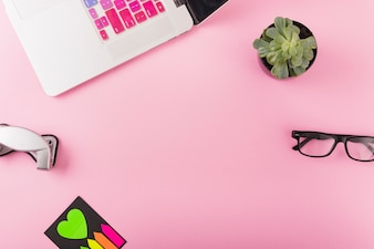 Laptop; hole puncher; potted plant and spectacles on pink background