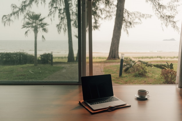 Laptop and hot coffee cup at door step with autumn beach view.