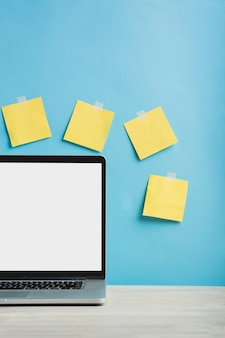 Laptop in front of yellow adhesive notes stucked on wall