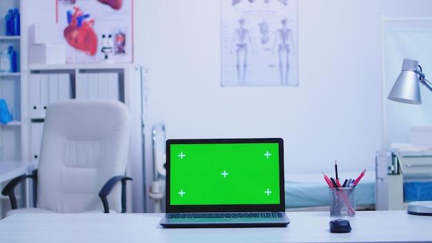 녹색 스크린이 있는 병원 캐비닛의 노트북과 보호 마스크를 들고 파란색 유니폼을 입은 간호사. 의료 클리닉에서 교체 가능한 화면이 있는 노트북.