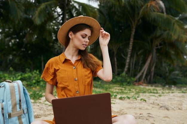 ラップトップ島の帽子と砂の上のバックパックで美しい女性