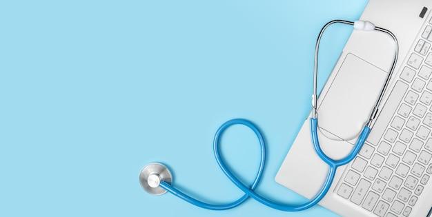 青い背景の上のラップトップキーボードと聴診器。オンライン医療、遠隔医療、医師のオンライン相談。遠隔医療の概念。コピースペース、上面図、バナー
