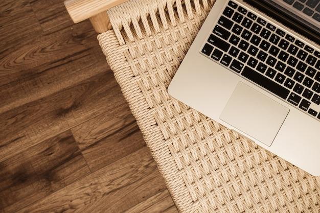 나무 바닥에 노트북 키보드와 고리 버들 세공 벤치입니다. 평면 위치, 평면도 홈 오피스 작업 공간